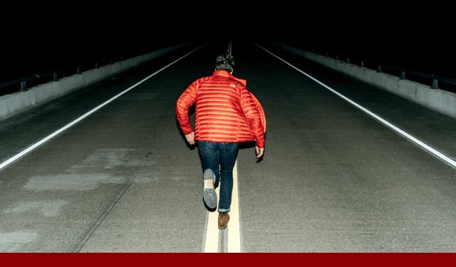 man running down dark road