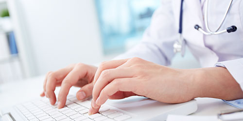 male physician typing on computer